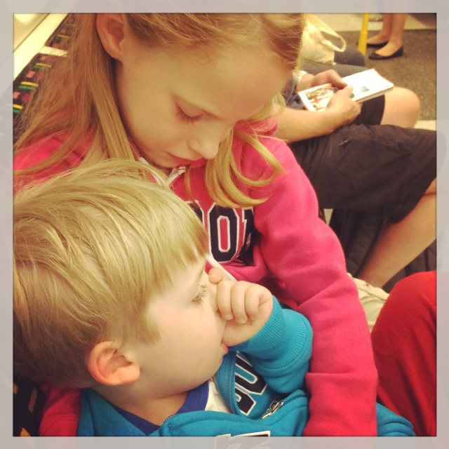 Big sister cuddling little brother on the Tube